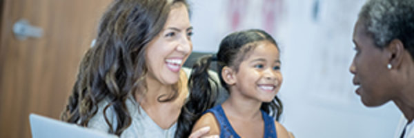 Mother and daughter smile during a doctor's consultation